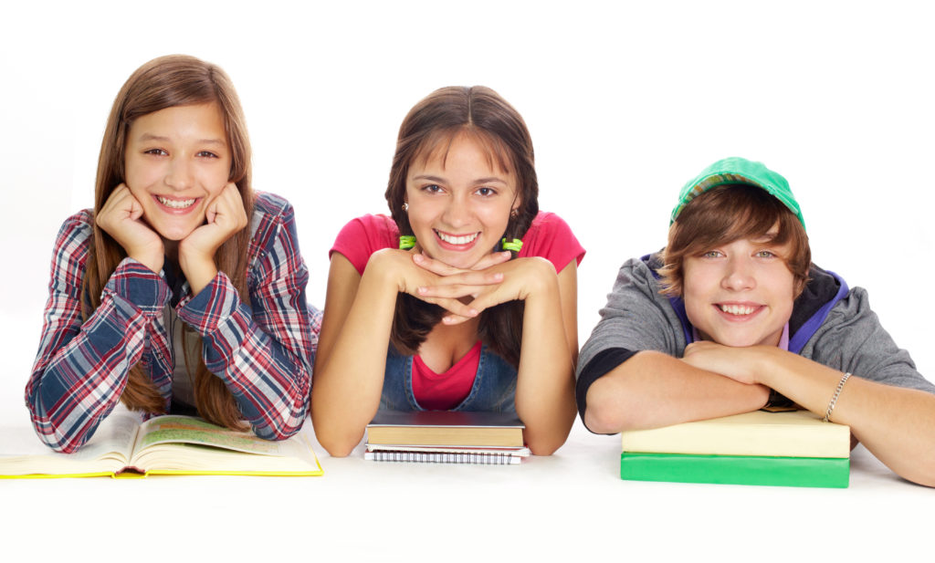 Cute teens with books smiling at camera